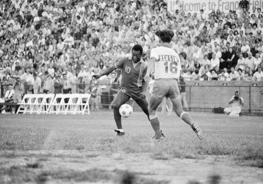 New York Cosmos star Pele shows a St. Louis sell-out crowd how its done as he gets the soccer ball around a St. Louis Stars player Gary Rensing during exhibition game on Sunday, August 10, 1975 at St. Louis.