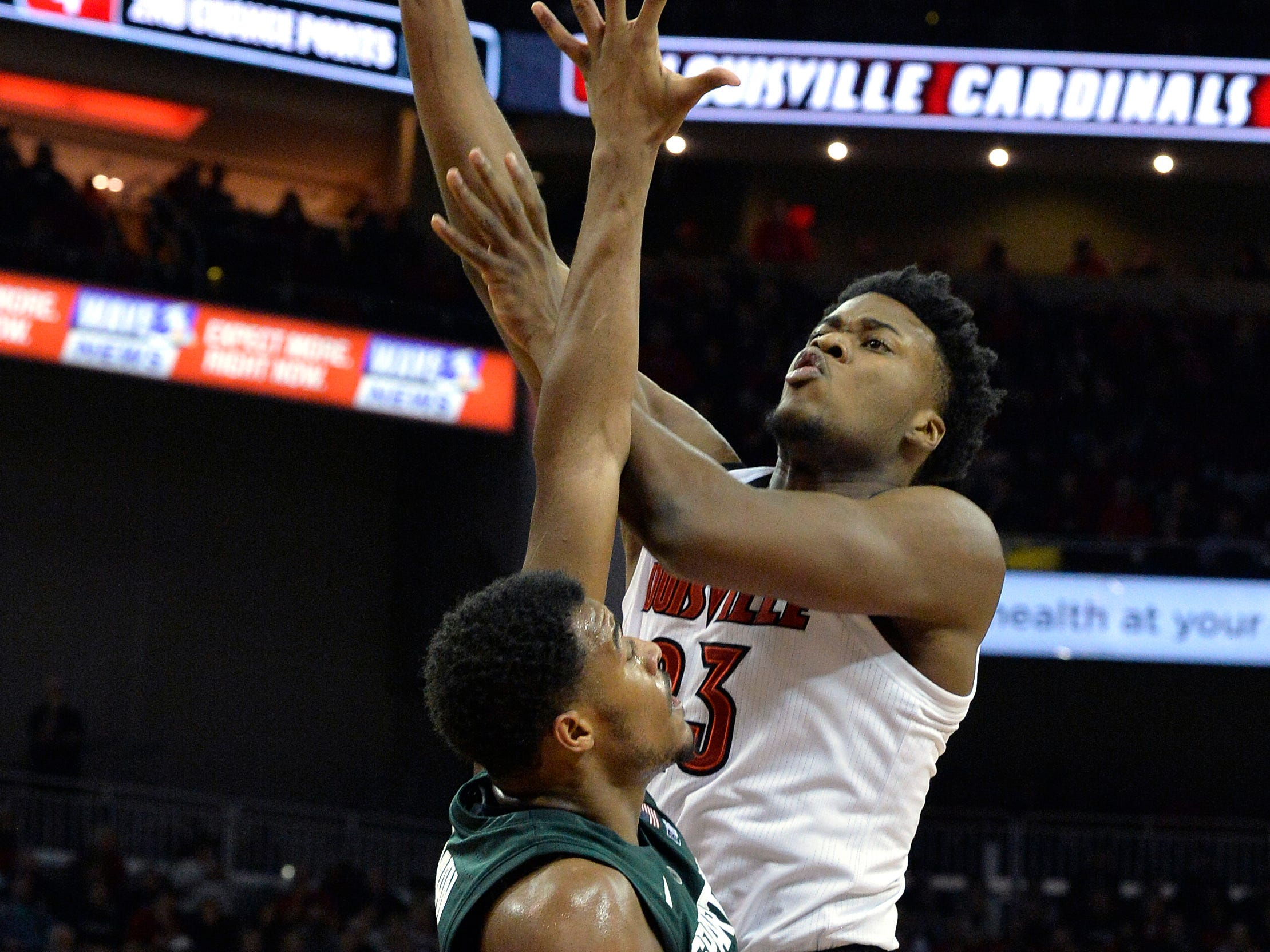Louisville center Steven Enoch (23) shoots over the defense of Michigan State forward Xavier Tillman (23) during the second half of an NCAA college basketball game, in Louisville, Ky., Tuesday, Nov. 27, 2018. Louisville won 82-78.