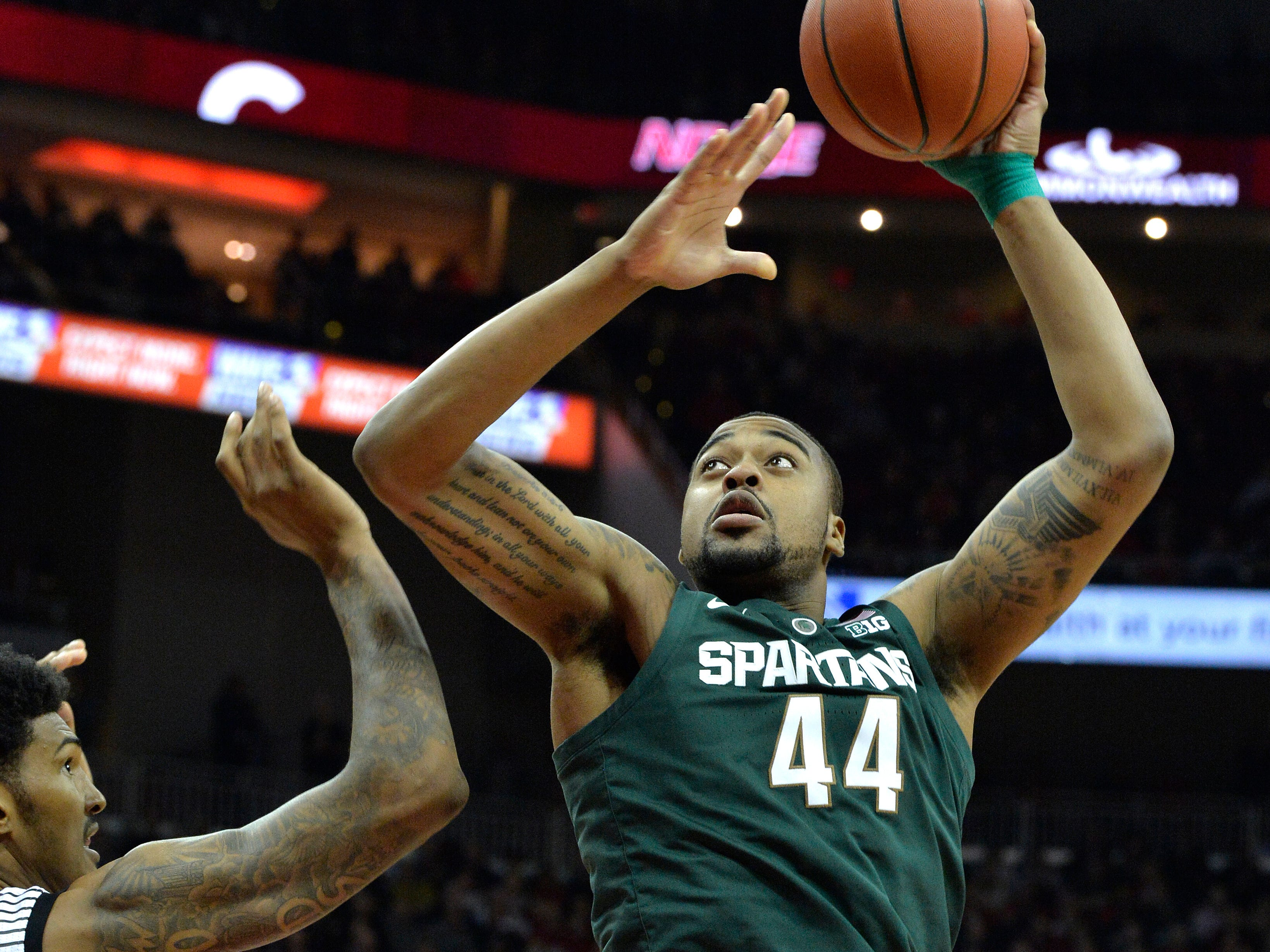 Michigan State forward Nick Ward (44) puts up a shot over Louisville center Malik Williams (5) during the first half of an NCAA college basketball game, in Louisville, Ky., Tuesday, Nov. 27, 2018.