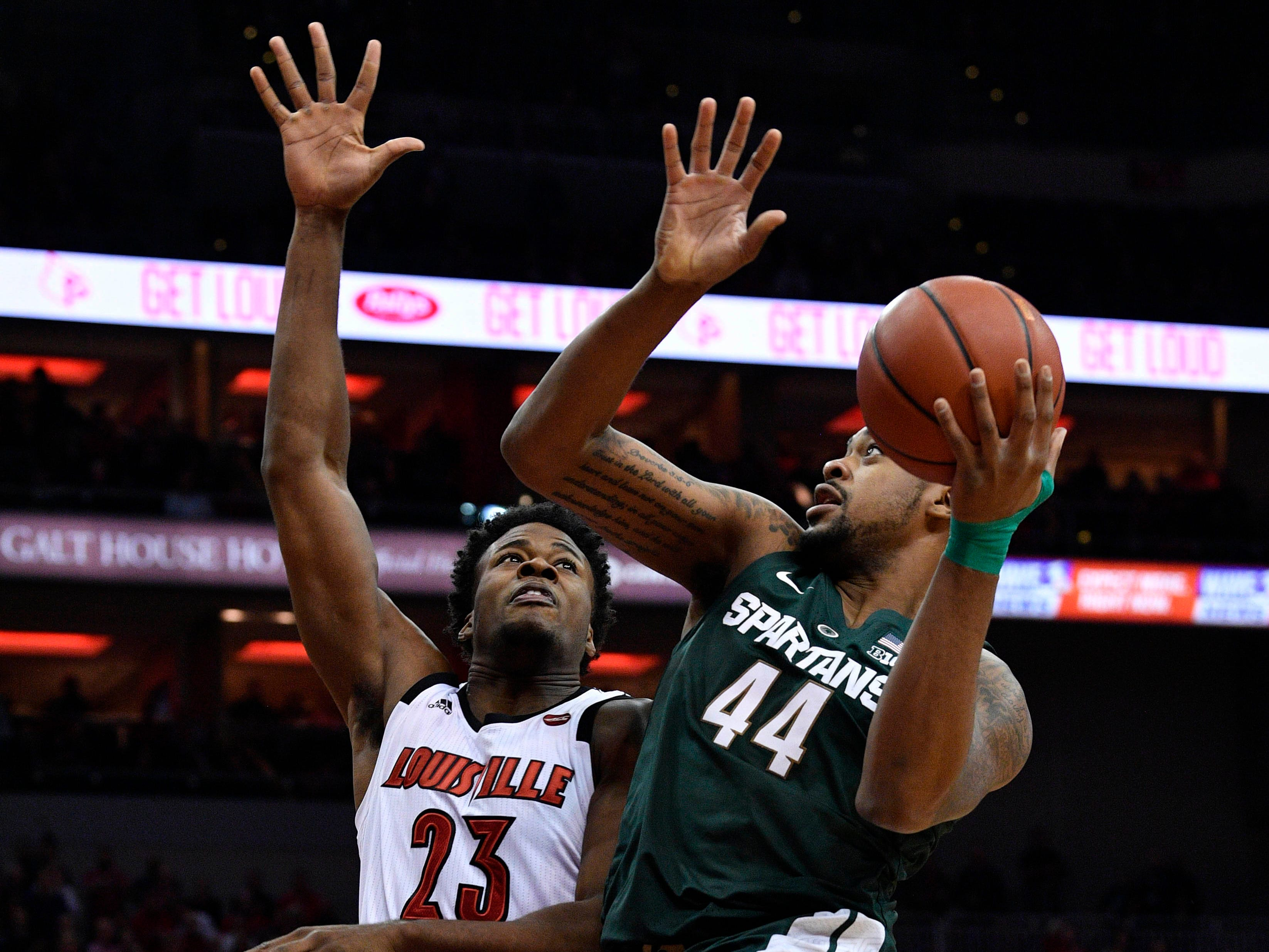 Louisville, KY, USA; Michigan State Spartans forward Nick Ward (44) shoots against Louisville Cardinals center Steven Enoch (23) during the first half at KFC Yum! Center.