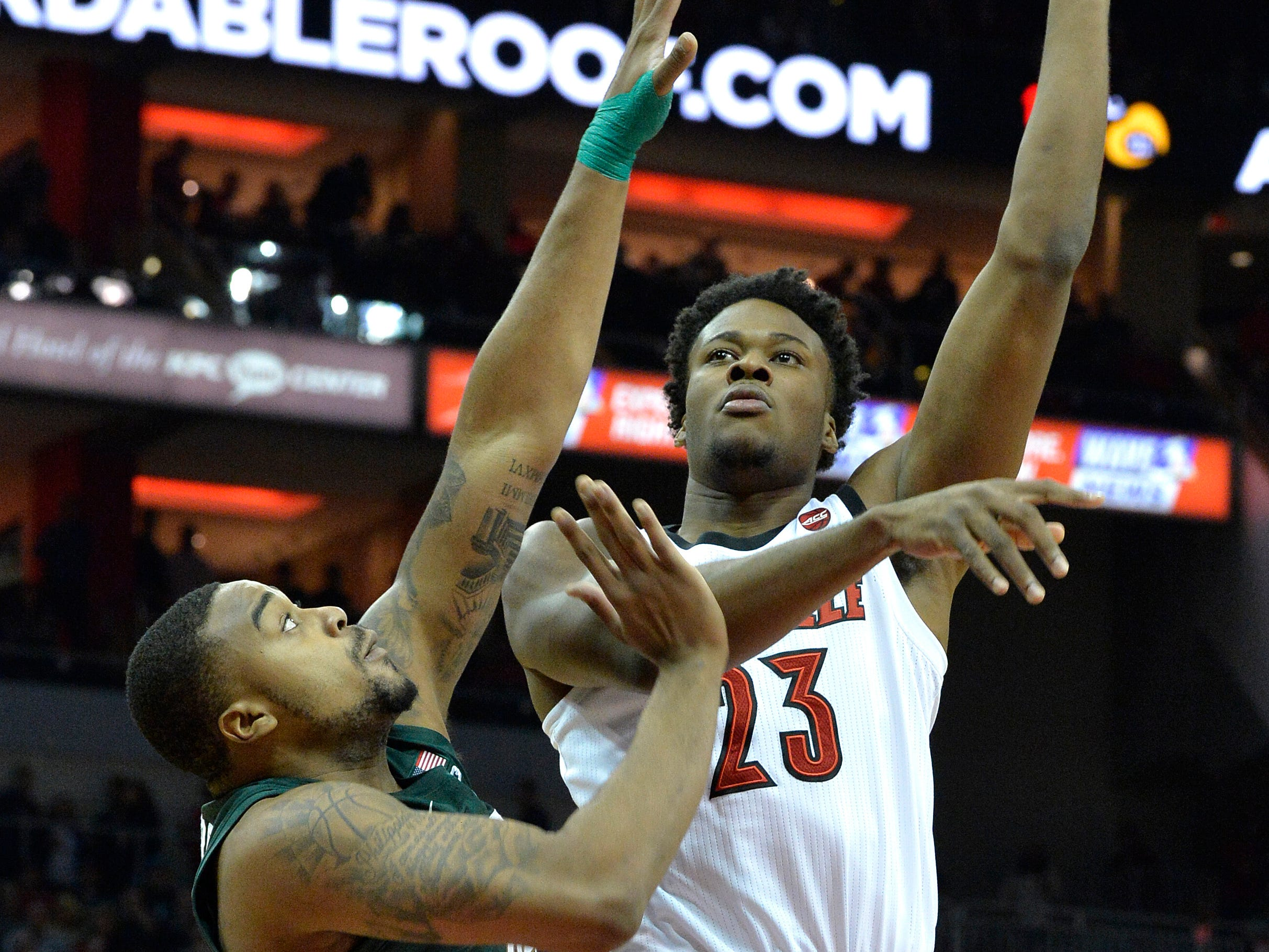 Louisville center Steven Enoch (23) shoots over the defense of Michigan State forward Nick Ward (44) during overtime of an NCAA college basketball game, in Louisville, Ky., Tuesday, Nov. 27, 2018. Louisville won 82-78.