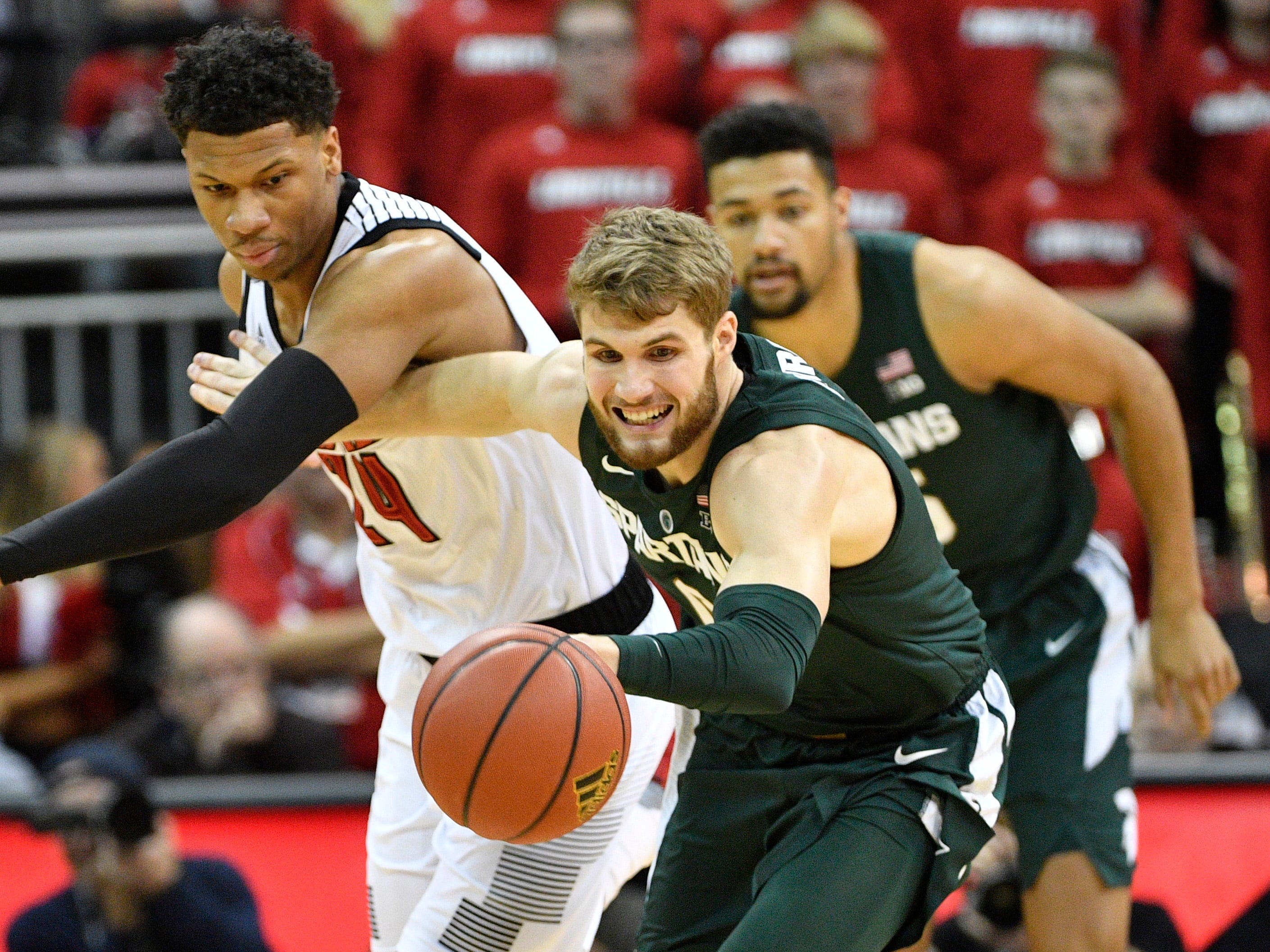 Michigan State Spartans forward Kyle Ahrens (0) scrambles for a loose ball with Louisville Cardinals forward Dwayne Sutton (24) during the first half at KFC Yum! Center.
