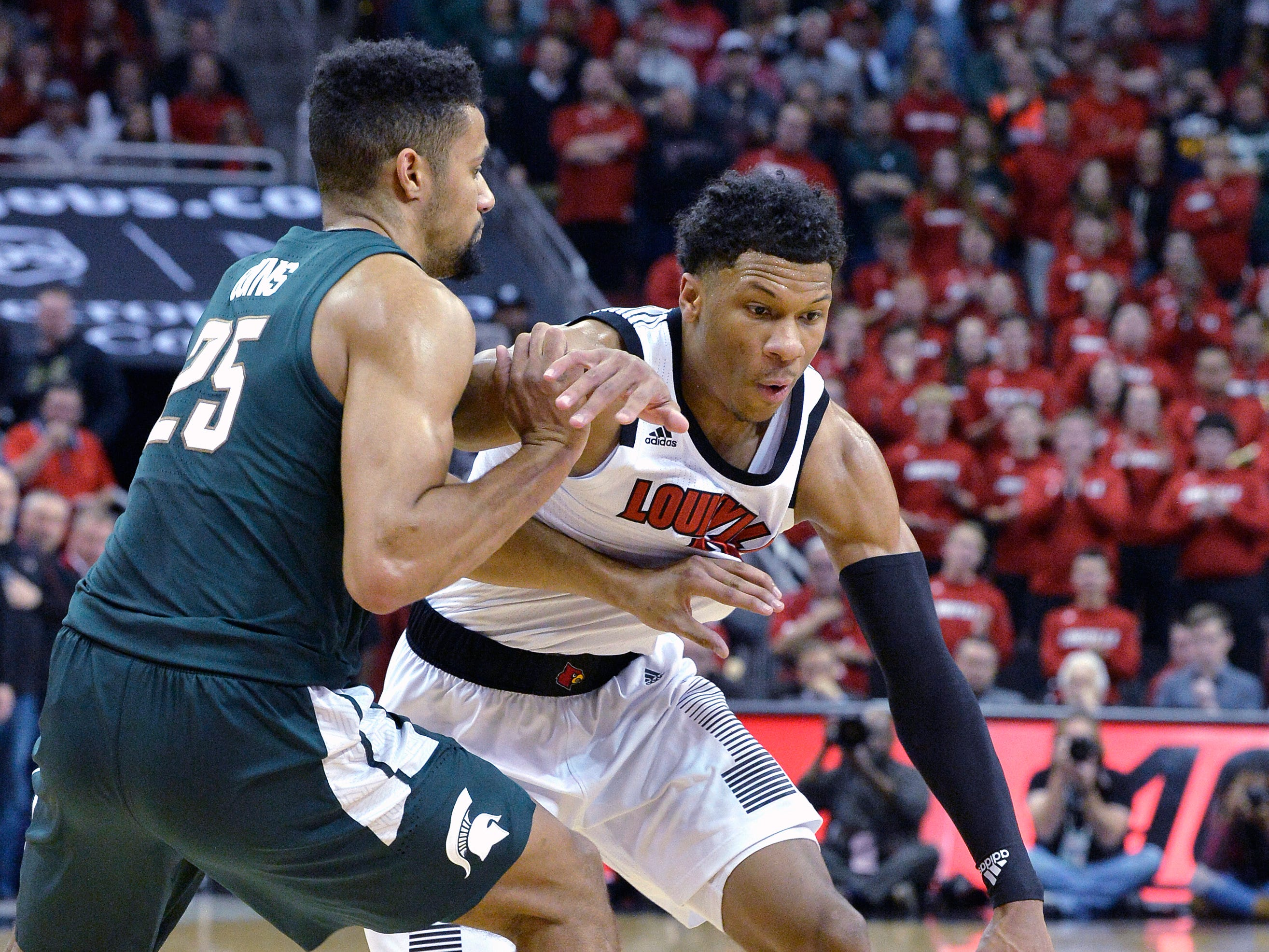 Louisville forward Dwayne Sutton (24) attempts to drive around the defense of Michigan State forward Kenny Goins (25) during the second half of an NCAA college basketball game, in Louisville, Ky., Tuesday, Nov. 27, 2018. Louisville won 82-78.