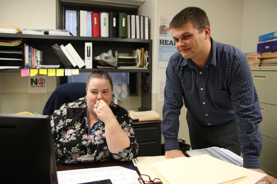 Ike Hickman and Jennifer Atwell look at information about their several assistance programs at the Community Action Commission of Erie, Huron and Richland Counties.
