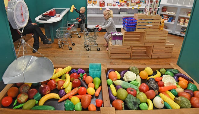 Grayce Metzger, 3, and Beckham Metger, 2, fill their carts with groceries while playing at the Little Buckeye Children's Museum on Wednesday.