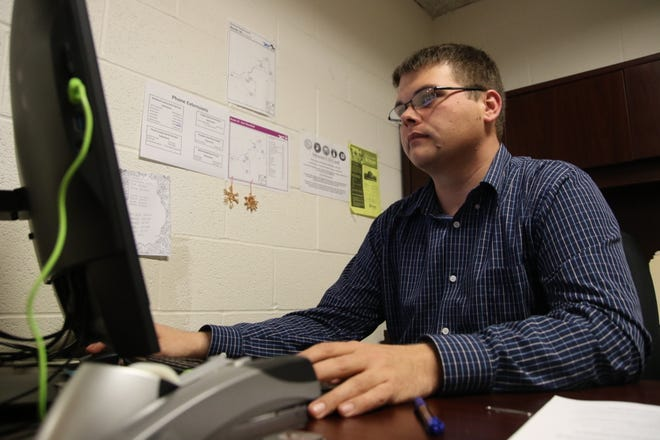 Ike Hickman, programs coordinator for Community Action Commission of Erie, Huron and Richland Counties, settles into his new office.