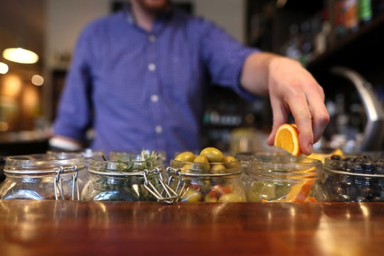 Bartender Daniel Quinian works on artisan cocktails, using fresh berries, mint and citrus elements at Ecco Restaurant in Midtown's Evergreen Historic District.