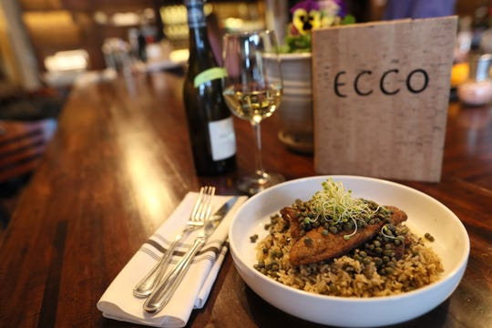 Branzino bass filet served with lemon and caper butter over basmati rice at Ecco Restaurant in Midtown's Evergreen Historic District.