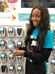 "At Kroger, the new ""Scan, Bag, Go"" service is a big timer saver.  Greeters like Miahri Merrell demonstrate how to use the scanner."