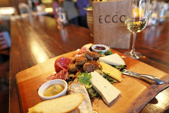 The 'Sampler Plate' charcuterie board with house-made Italian fennel sausage, an assortment of cured meats, and a variety of cheeses including manchego, Taleggio, and Cambozola at Ecco Restaurant in Midtown's Evergreen Historic District.