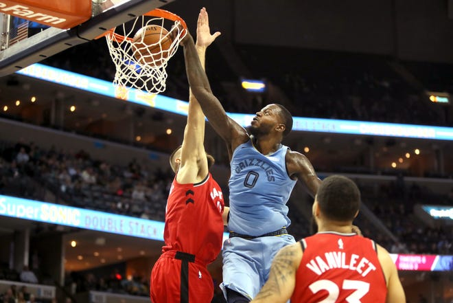 The Grizzlies' JaMychal Green dunks over Raptors defender Jonas Valanciunas on Tuesday. Memphis squandered a double-digit lead in the 122-114 loss to Toronto.