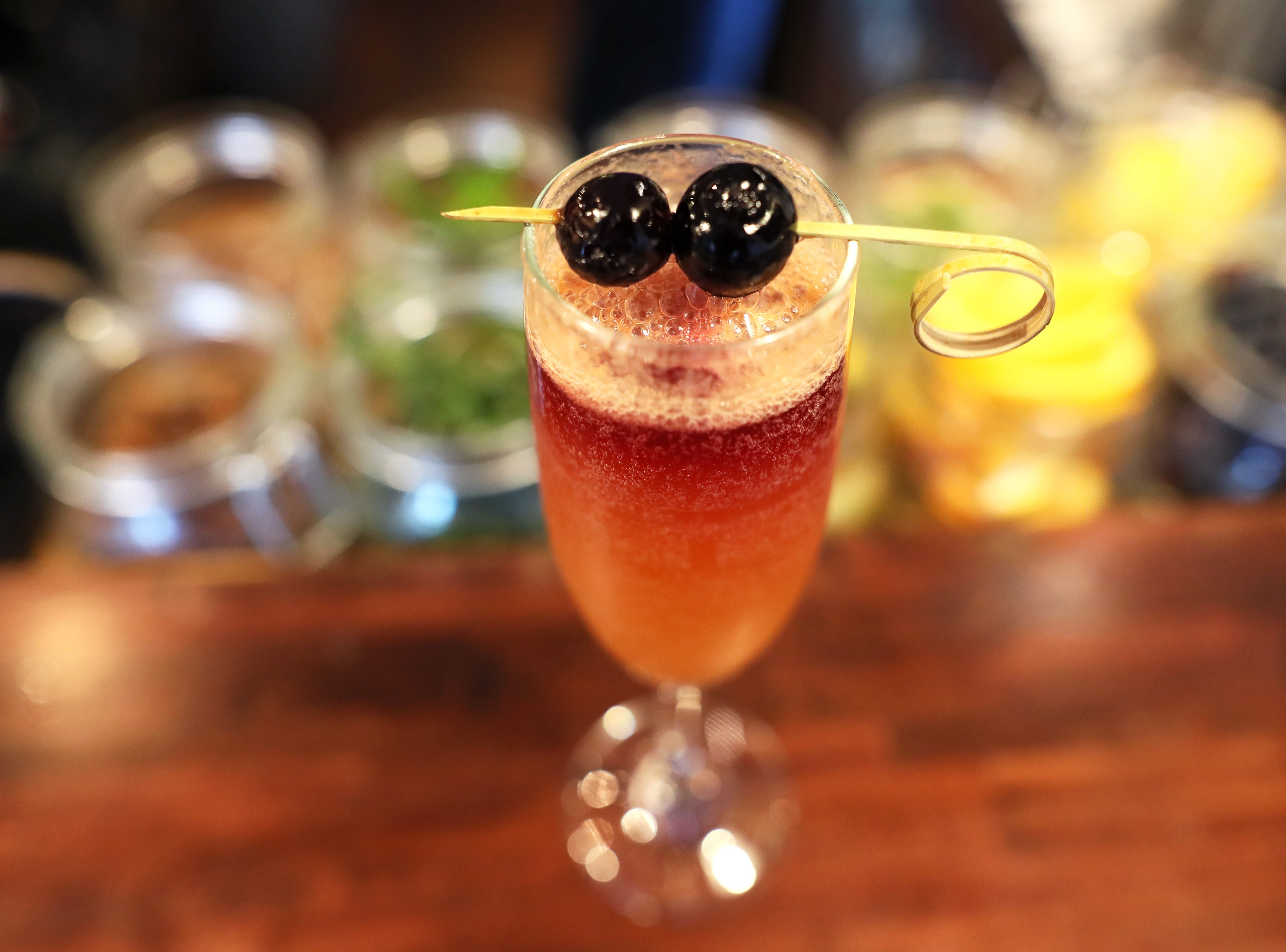 A-Wop-Bop-A-Loo-Lop cocktail with vodka, plum, aperol, lemon, cava, pinot noir, garnished with blue berries at Ecco Restaurant in Midtown's Evergreen Historic District.