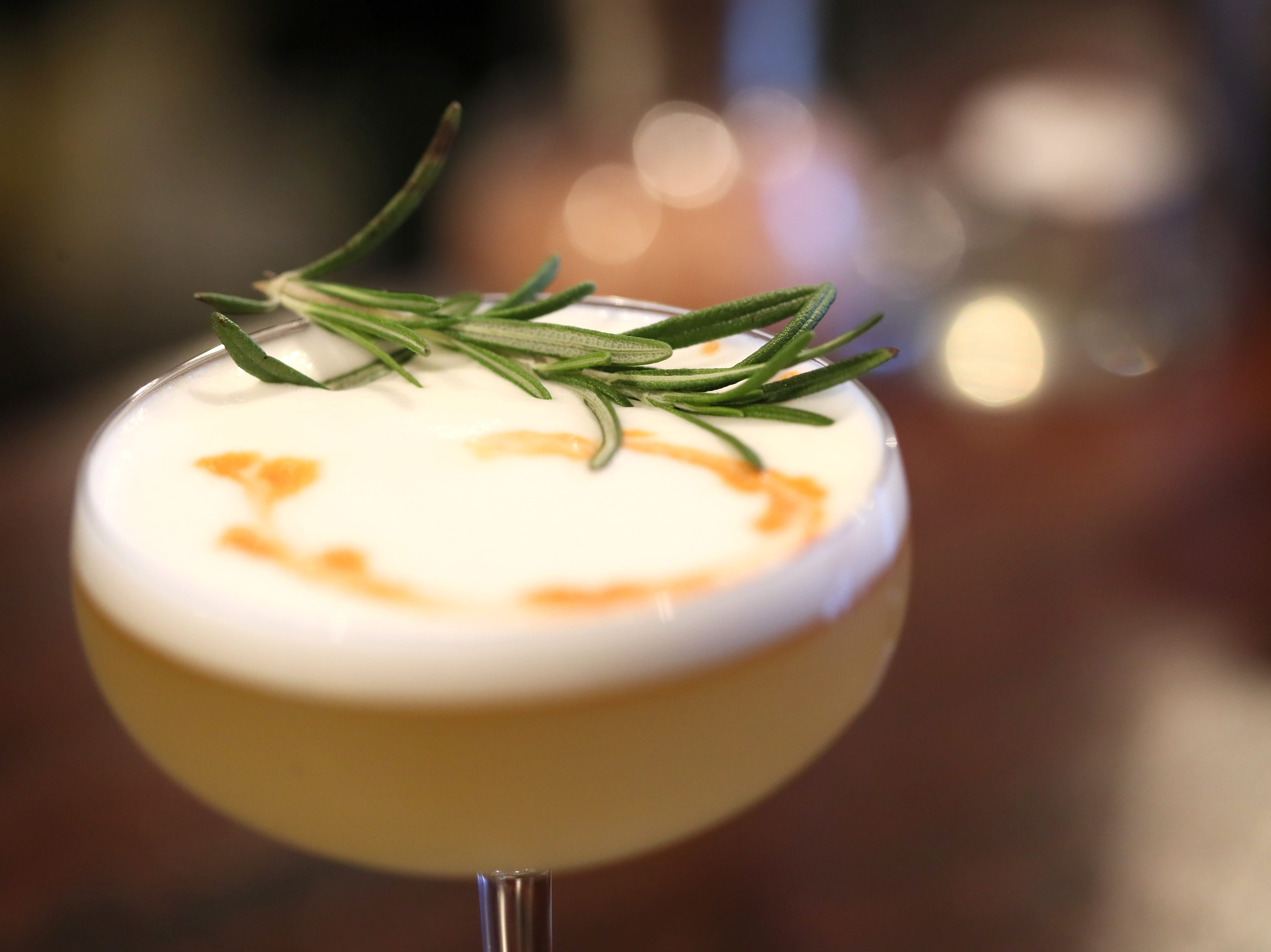 A Rocky the Flying Squirrel cocktail, with amaretto, rhubarb bitters, lemon, egg white, cinnamon and a rosemary garnish at Ecco Restaurant in Midtown's Evergreen Historic District.
