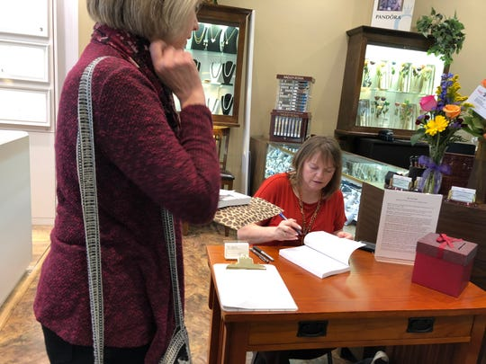 "Local writer Toni Lepeska signs a copy of ""Grief Dialogues: The Book"" on Nov. 16 at Master Jewelers in Olive Branch. Lepeska contributed to the book."