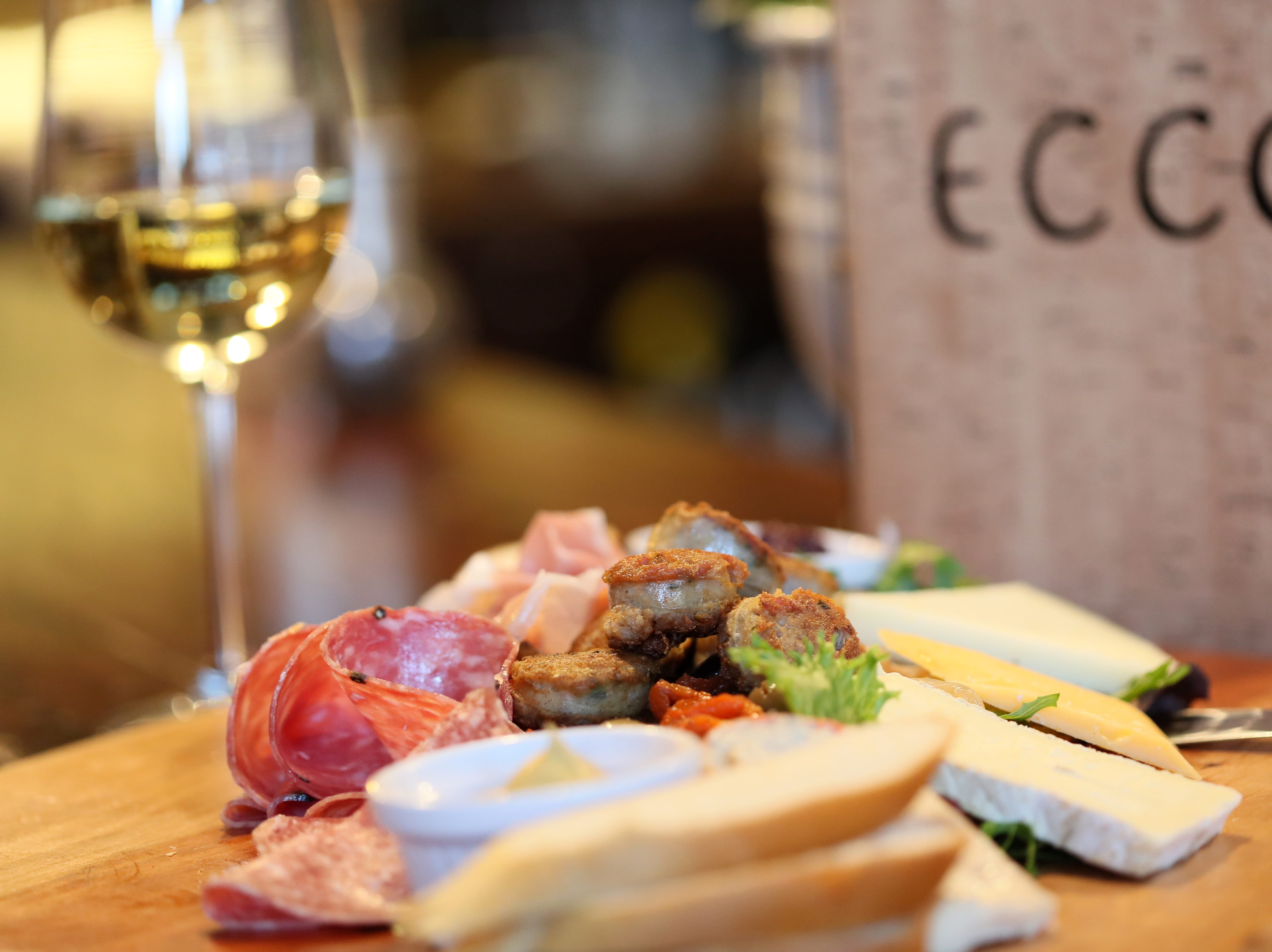 Charcuterie board with house-made Italian fennel sausage, an assortment of cured meats, and a variety of cheeses including manchego, taleggio, and cambazola at Ecco Restaurant in Midtown's Evergreen Historic District.