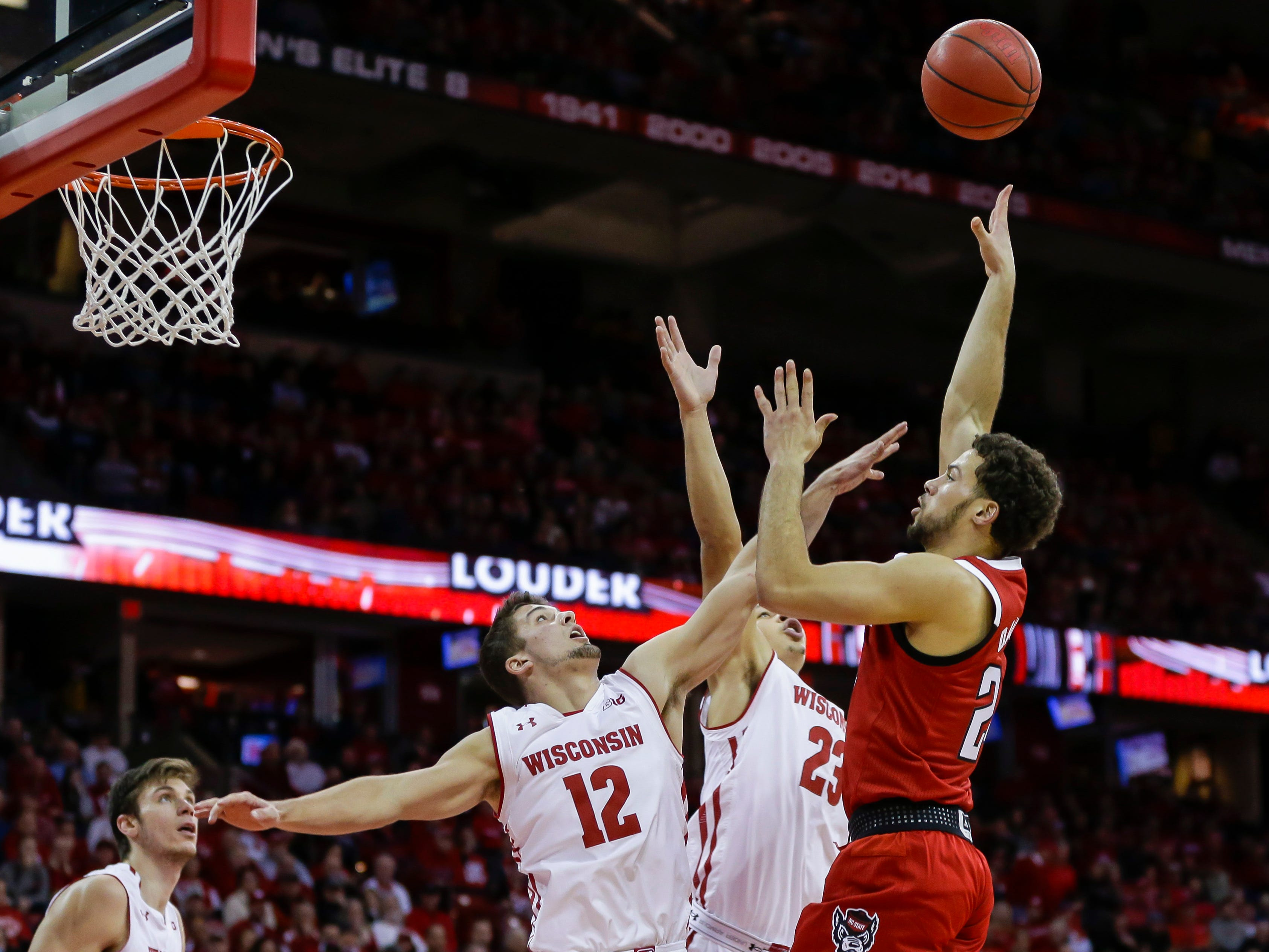 North Carolina State's Devon Daniels, right, shoots over  Wisconsin's Trevor Anderson (12) and Kobe King (23).