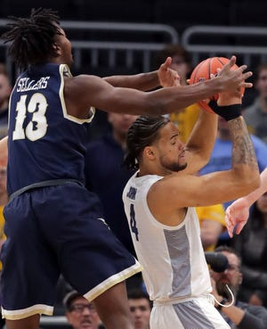 Marquette forward Theo John (4) and Charleston Southern forward Timmy Sellers (13) compete for a rebound.