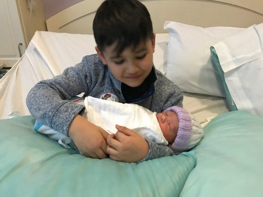 Seven-year-old Mason Cardona-Brunk of Brookfield, cradles his new baby sister who isn't even a day old in his arms. Tiny Layla was born in the parking lot of the Country Inn & Suites, 1250 S. Moorland Road, Brookfield, while parents Jason Brunk and his wife Mayda Cardona pulled over en route to Aurora West Allis Medical Center.