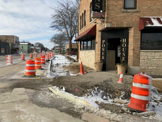 """The """"open"""" sign bravely tries to attract patrons to Braun's Power House at 71st and National. Business is down 50 percent, owner Joe Braun said. National Avenue has been under construction all summer and the sidewalks were ripped out a month ago. Crews have tried to improve sidewalk access by filling in with an earth and gravel mix."""