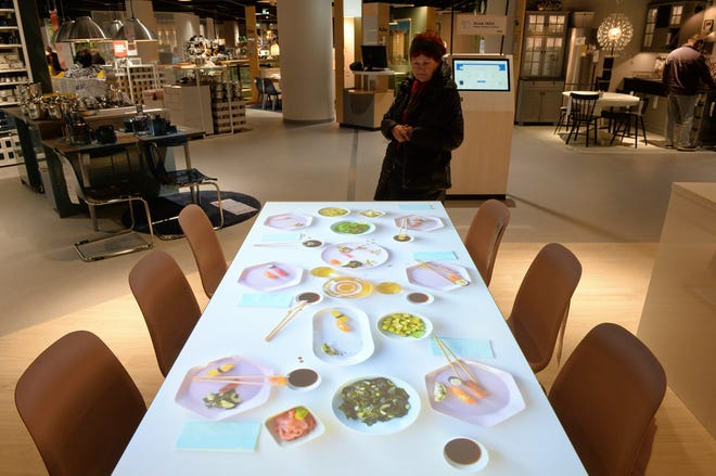 A customer looks at a table with a projected arrangement Thursday at a new Ikea store, in Warsaw, Poland. The store, recently opened in a shopping mall, is part of a global strategy by the Swedish furniture chain to adapt to a changing consumer environment by opening small, accessible stores in city centers to complement the traditional large out-of-town store stores.