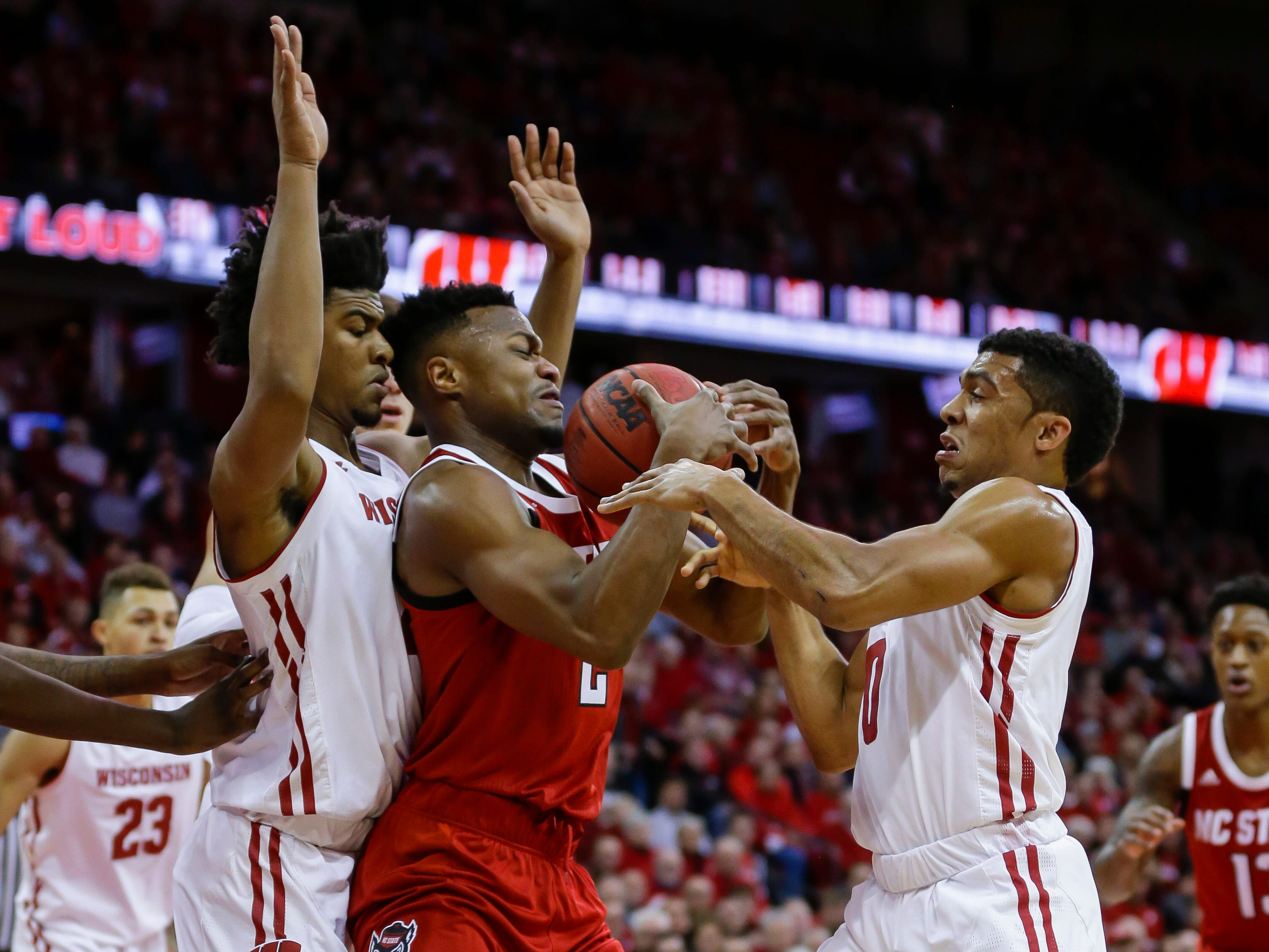 North Carolina State's Torin Dorn  is doubled by Wisconsin's Aleem Ford (left) and D'Mitrik Trice.