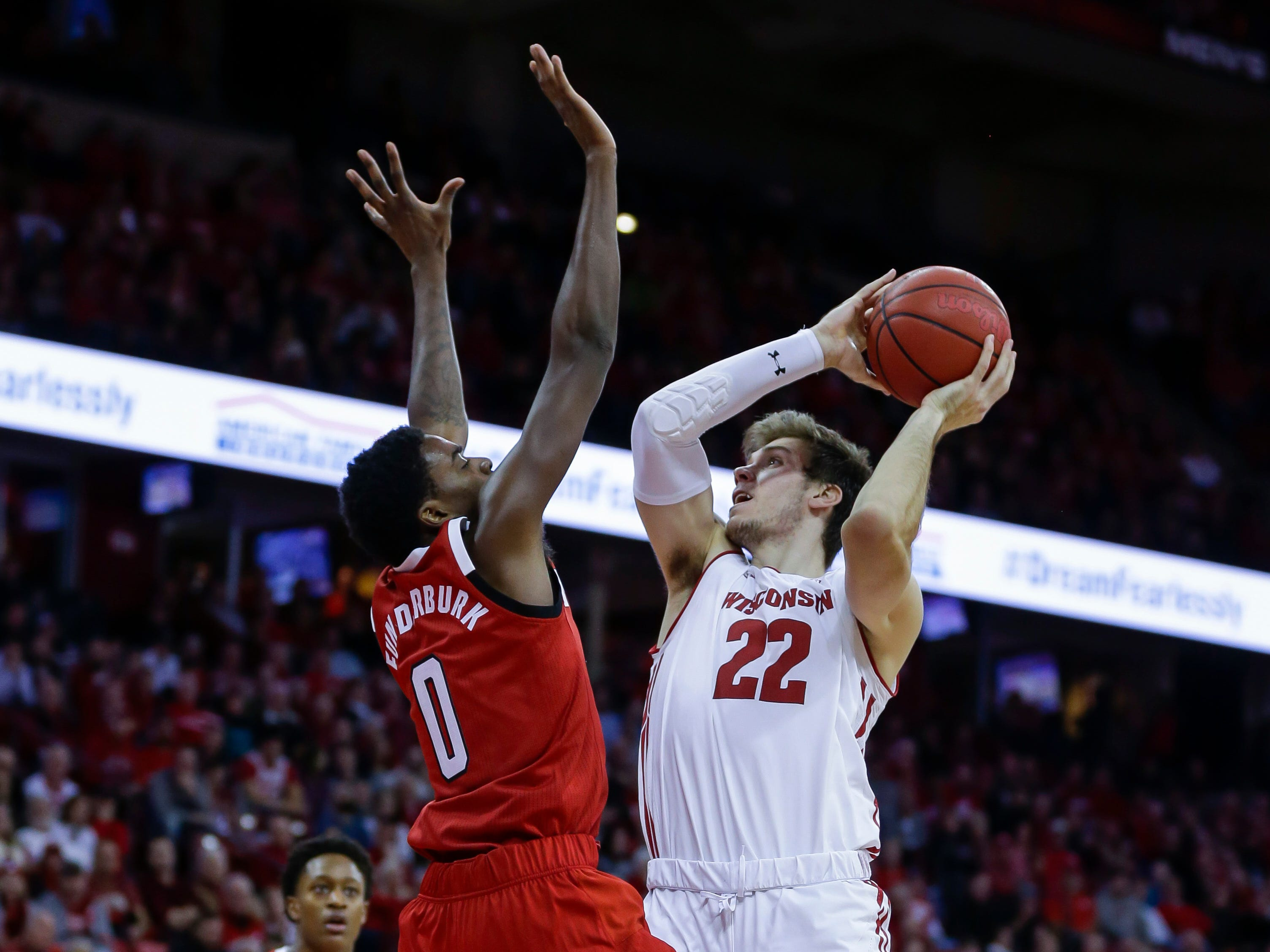 Wisconsin's Ethan Happ looks to get a shot over North Carolina State's DJ Funderburk.