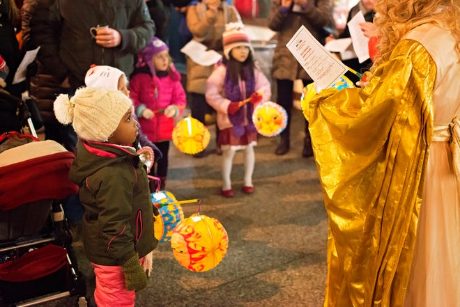 Children participate in a lantern parade and singalong with the Christkind during a Christkindlemarket.