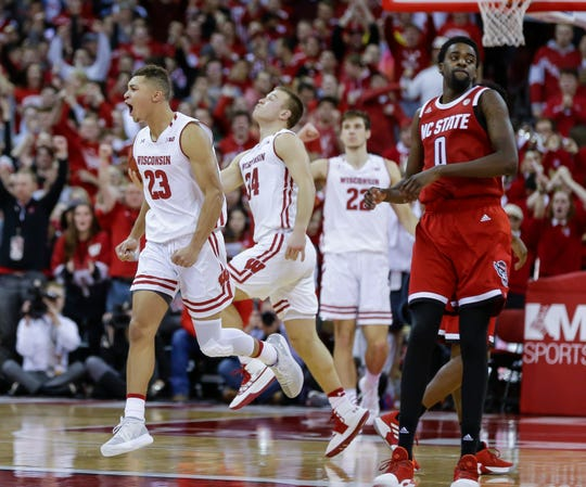 Wisconsin's Kobe King (left), Brad Davison (center) and Ethan Happ  celebrate as North Carolina State's DJ Funderburk walks off the court after the Badgers' victory.