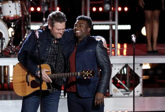 "Blake Shelton hugs Montgomery singer Kirk Jay on stage during Tuesday's episode of ""The Voice."""