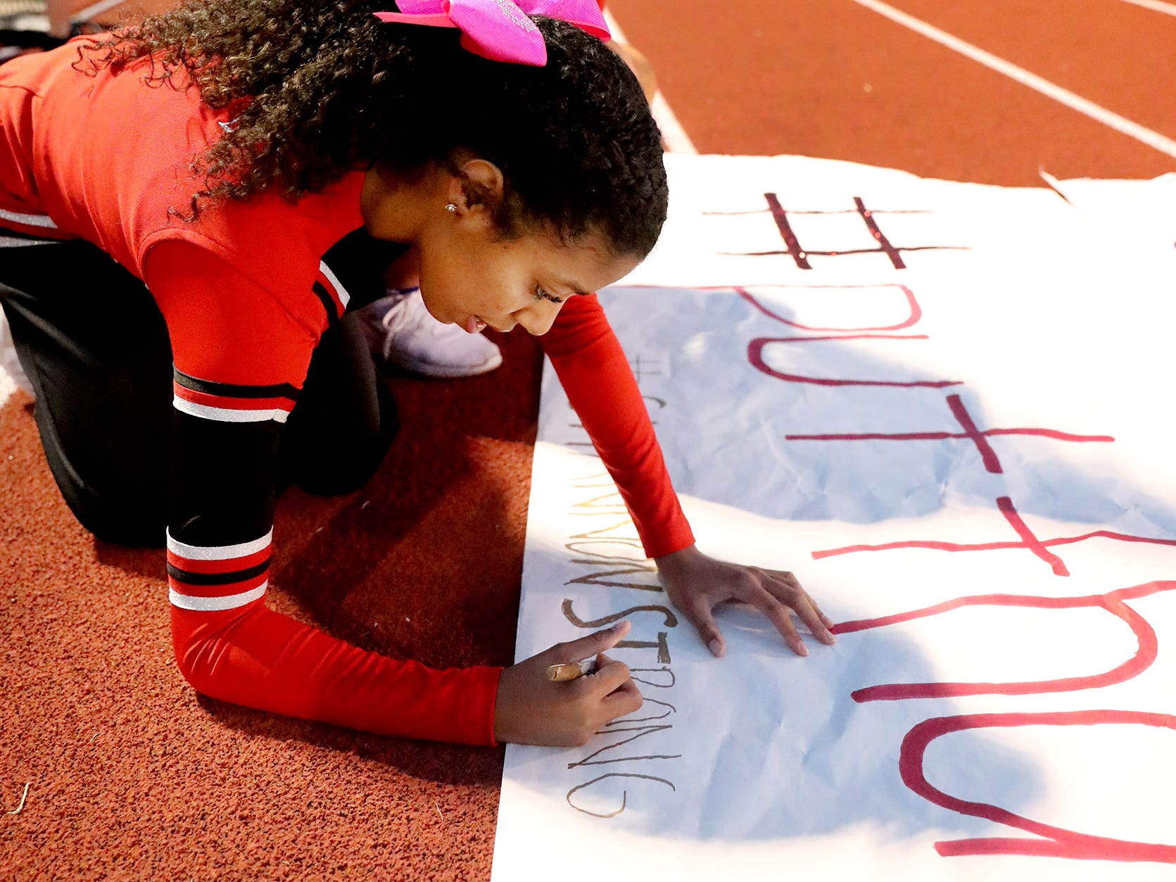 Stewarts Creek senior cheerleaders Jewell Windrow writes #ShannonStrong on their sign in support of the Smyrna Coach Matt Williams' wife who is battling cancer before the game against Smyrna on Friday, Oct. 12, 2018. Senior Creek cheerleader Leanne Ott watches Windrow.