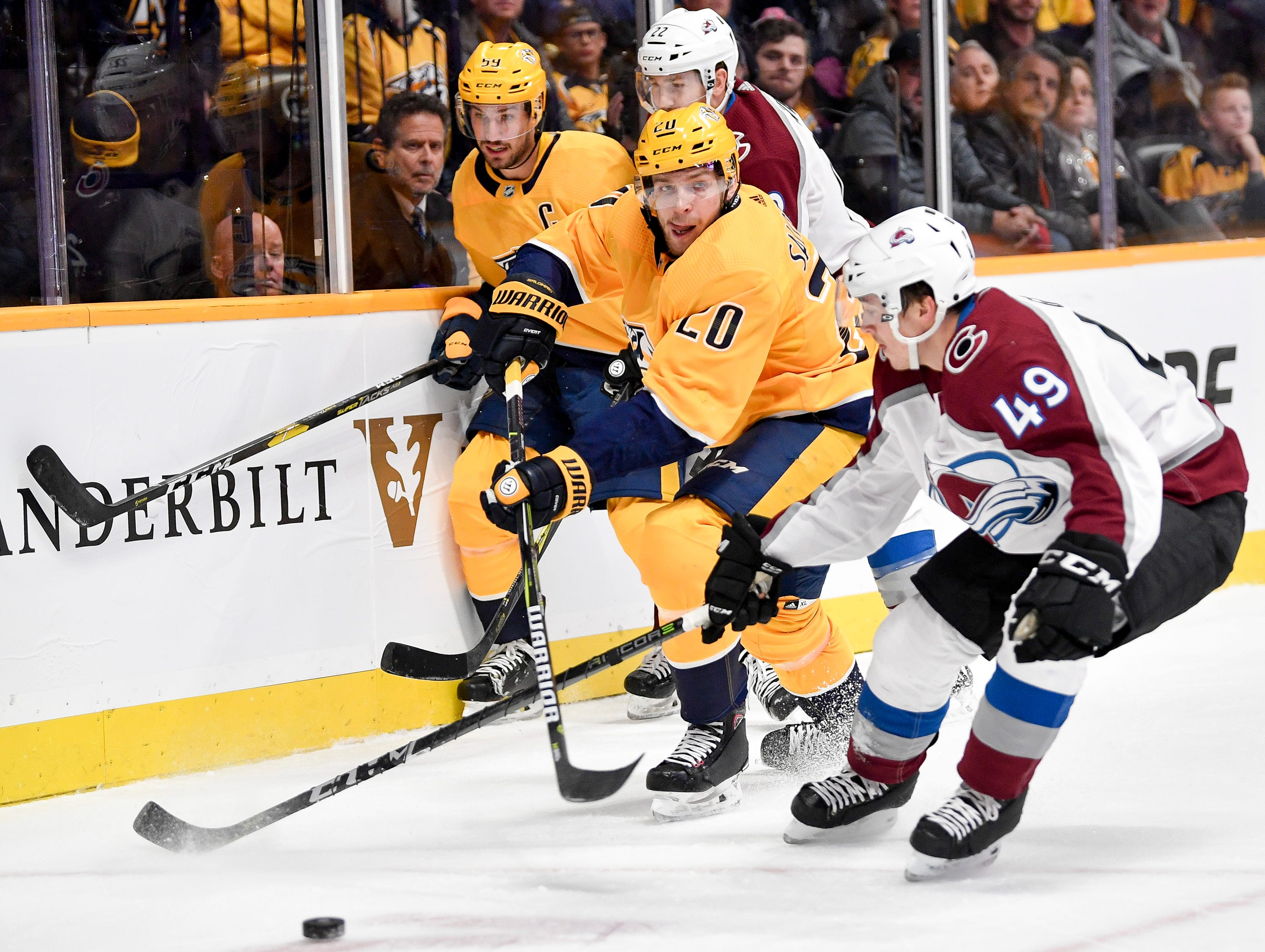 Nashville Predators right wing Miikka Salomaki (20) fights for the puck with Colorado Avalanche defenseman Samuel Girard (49) during the first period at Bridgestone Arena in Nashville, Tenn., Tuesday, Nov. 27, 2018.