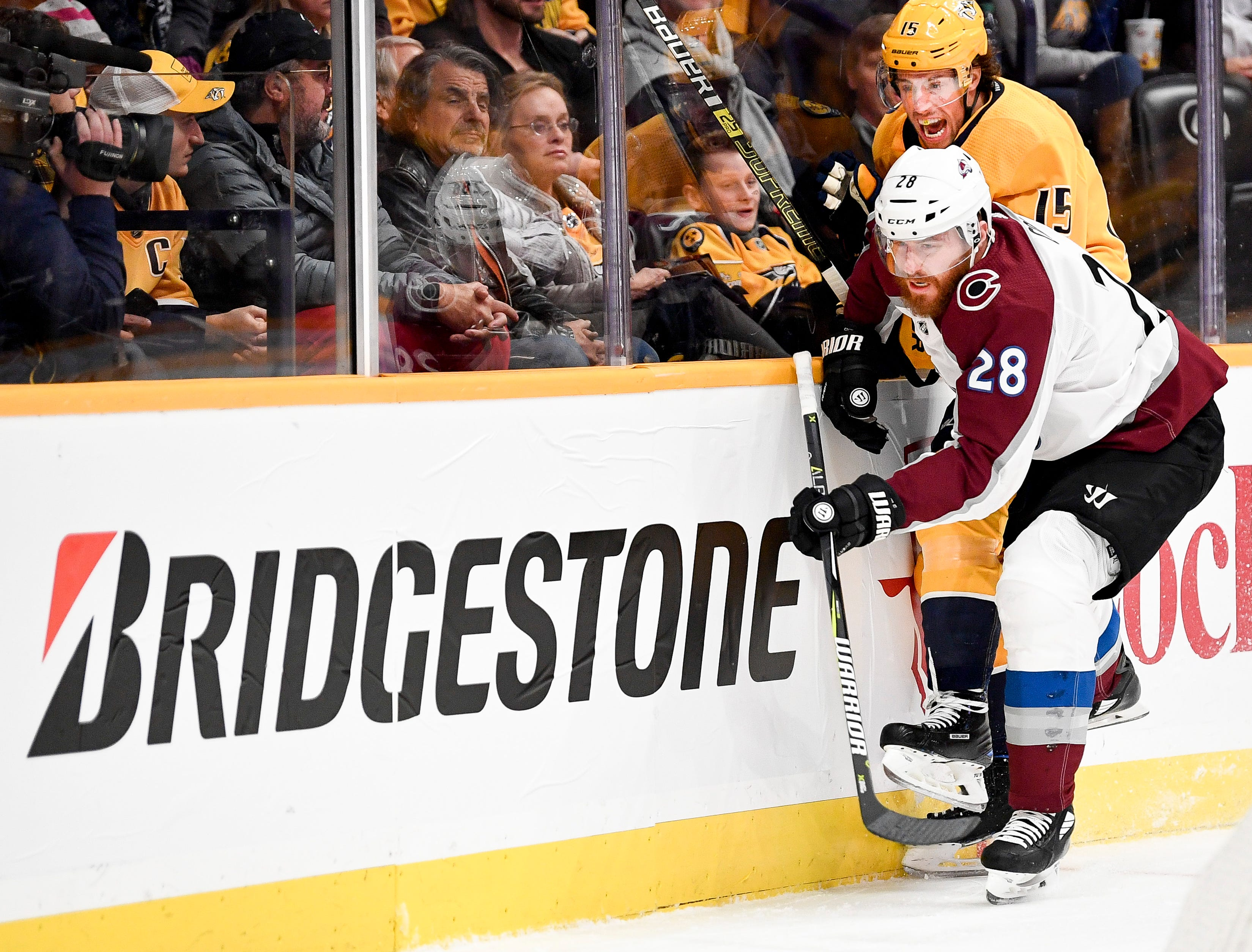 Nashville Predators right wing Craig Smith (15) battles for the puck with Colorado Avalanche defenseman Ian Cole (28) during the first period at Bridgestone Arena in Nashville, Tenn., Tuesday, Nov. 27, 2018.