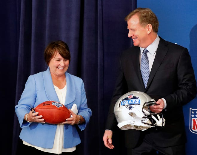 Tennessee Titans owner Amy Adams Strunk holds a football as she and NFL commissioner Roger Goodell prepare for a photo after it was announced that Nashville will host the 2019 NFL draft during the NFL owner's spring meeting Wednesday, May 23, 2018, in Atlanta.
