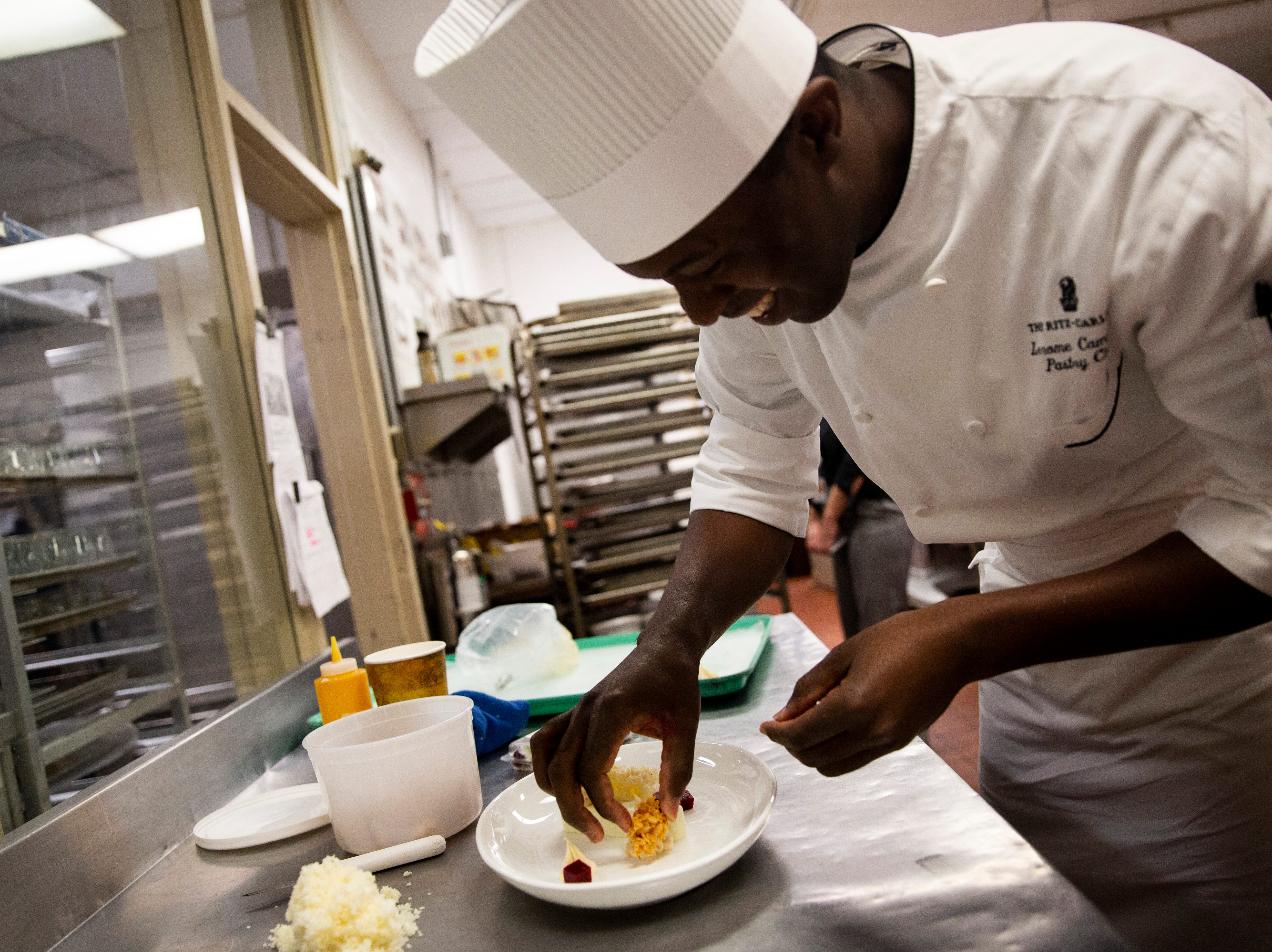 "Pastry Chef Lerome Campbell prepares a plated dessert that features a micro sponge cake on Wednesday, Nov. 28, 2018, at the Ritz-Carlton in Naples. Campbell is a contestant on the Food Network's ""Holiday Baking Championship"" and used his micro sponge cake, which is cooked in the microwave, to impress the judges in one episode."