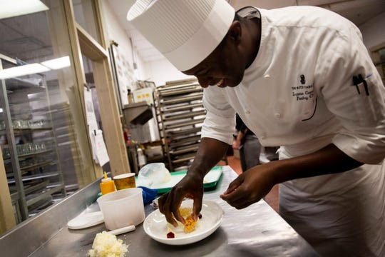 """Pastry Chef Lerome Campbell prepares a plated dessert that features a micro sponge cake on Wednesday, November 28, 2018, at the Ritz-Carlton in Naples. Campbell is a contestant on Food Network's """"Holiday Baking Championship,"""" and used his micro sponge cake, which is cooked in the microwave, to impress the judges in one episode."""