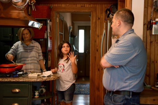 Bella talks with her grandmother, Madeline Caminiti, and father, Frank Clare, as Caminiti prepares a family favorite, spaghetti and meatballs.