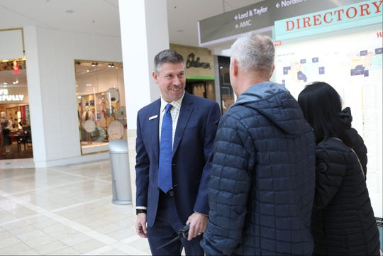 Jay Daly, manager of the Westfield Garden State Plaza Mall, helps a customer find a store