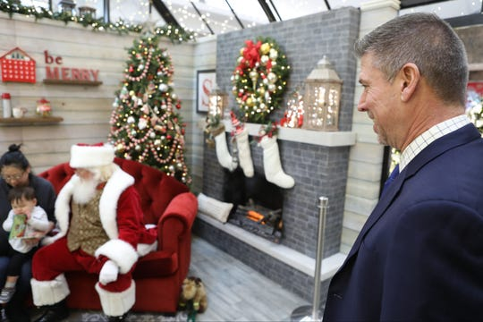 Jay Daly, manager of the Westfield Garden State Plaza Mall, watches as a child is photographed with Santa Claus.