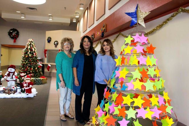 From left, Las Cruces Public Schools Migrant Education employees Rosalinda Carreón-Altamirano, Iggy Campos and Marie Garces pose next to the department's 'Wish Upon a Star' tree in the lobby of the LCPS Administration Building.