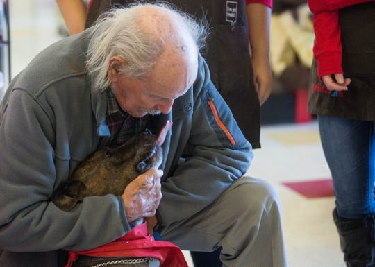 "Henry Evarts, gives his dog Sugar Plum a hug as she licks him during  a check presentation at PetCo on Lohman, Wednesday November 28, 2018.  PetCo is giving $10,000 to Animal Village of New Mexico, the orginization that Evarts adopted Sugar Plum from. Evarts said when asked about ""Sugar"" ""Well I'm 90 years old and when I'm with Sugar she makes me feel at least 89, she is a good dog...she is good company."""
