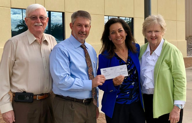 Craig Buchanan (second from left) presents a $6,000 investment to members of The Bridge of Southern New Mexico's leadership – (from left) Les Baldock, Tracey Bryan, and Dr. Susan Brown.