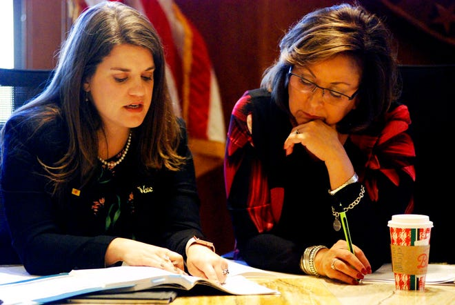 New Mexico Gov. Susana Martinez, right, and Secretary of State Maggie Toulouse Oliver, left, certify election results and order recounts in a handful of state House races in Santa Fe, N.M., on Tuesday, Nov. 27, 2018, as members of the State Canvassing Board.