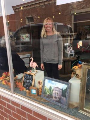 Guild member Miranda Semmerling arranges her display in the window of the Grant County Art Guild Gallery
