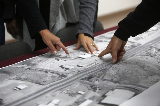People point to a location on a map of future construction on U.S. Highway 64 Wednesday at McGee Park in Farmington.