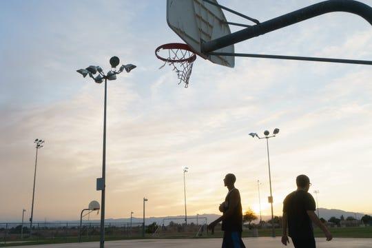 Andre Walker y Noor Hijazi juegan baloncesto en un parque al lado del Río Nuevo en Calexico.