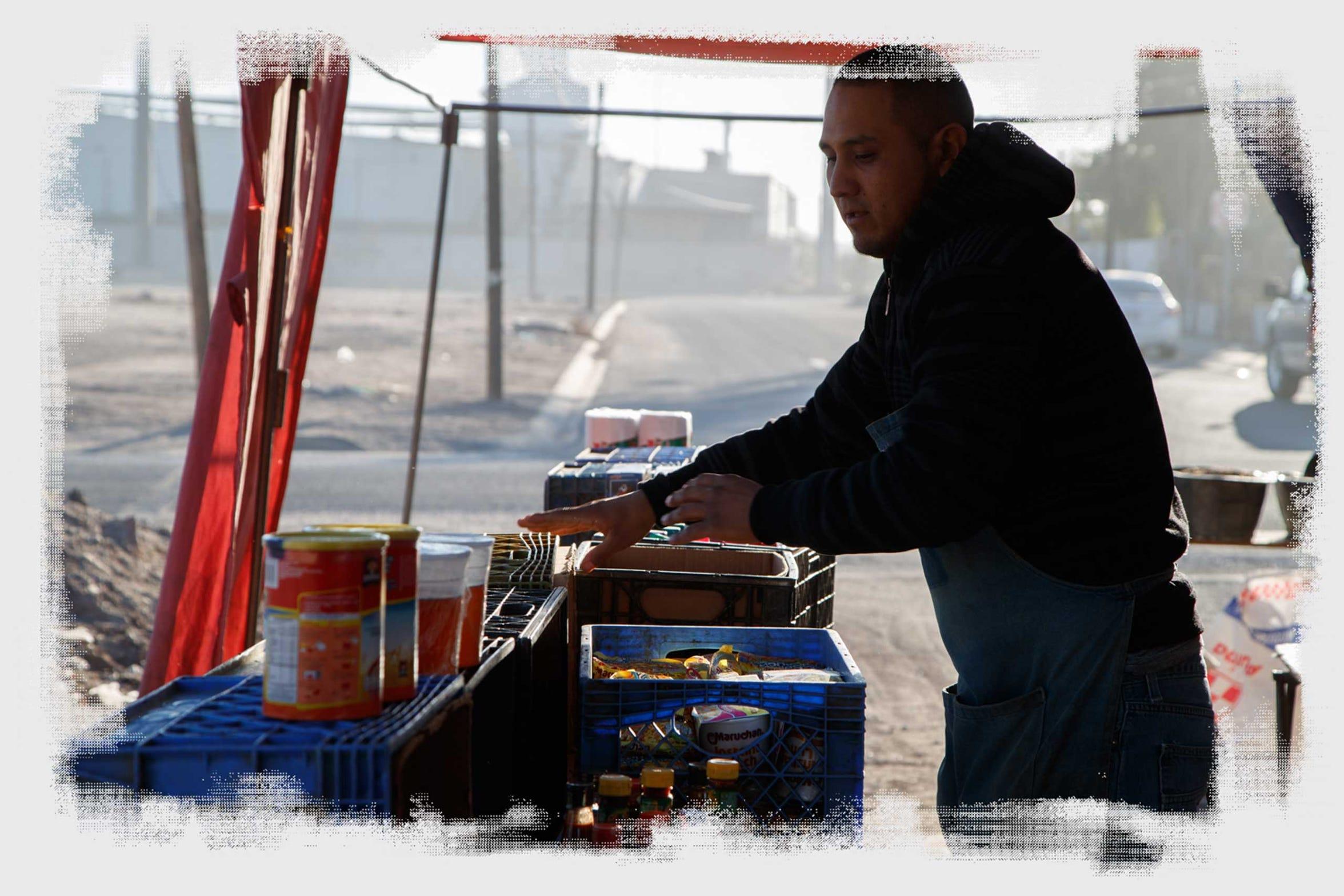 Luis Alberto Rodríguez distribuye comida en un pequeño mercado callejero, situado en un vecindario rodeado por varias fábricas en Mexicali.