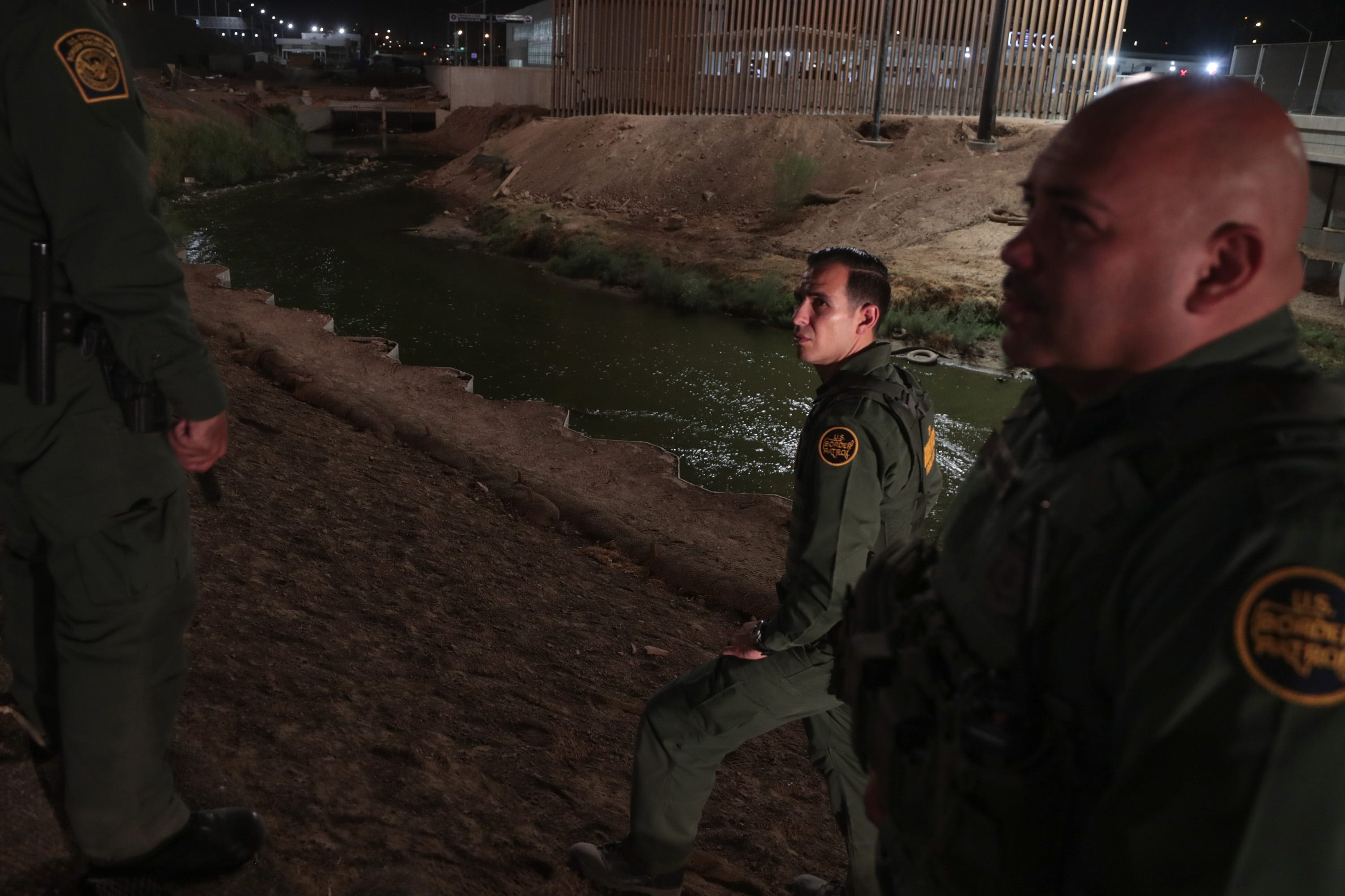 Border Patrol agents Ruben Sigala, center, and Jose Enriquez, right, talk with other agents while patrolling the New River in Calexico on Sept. 19, 2018.