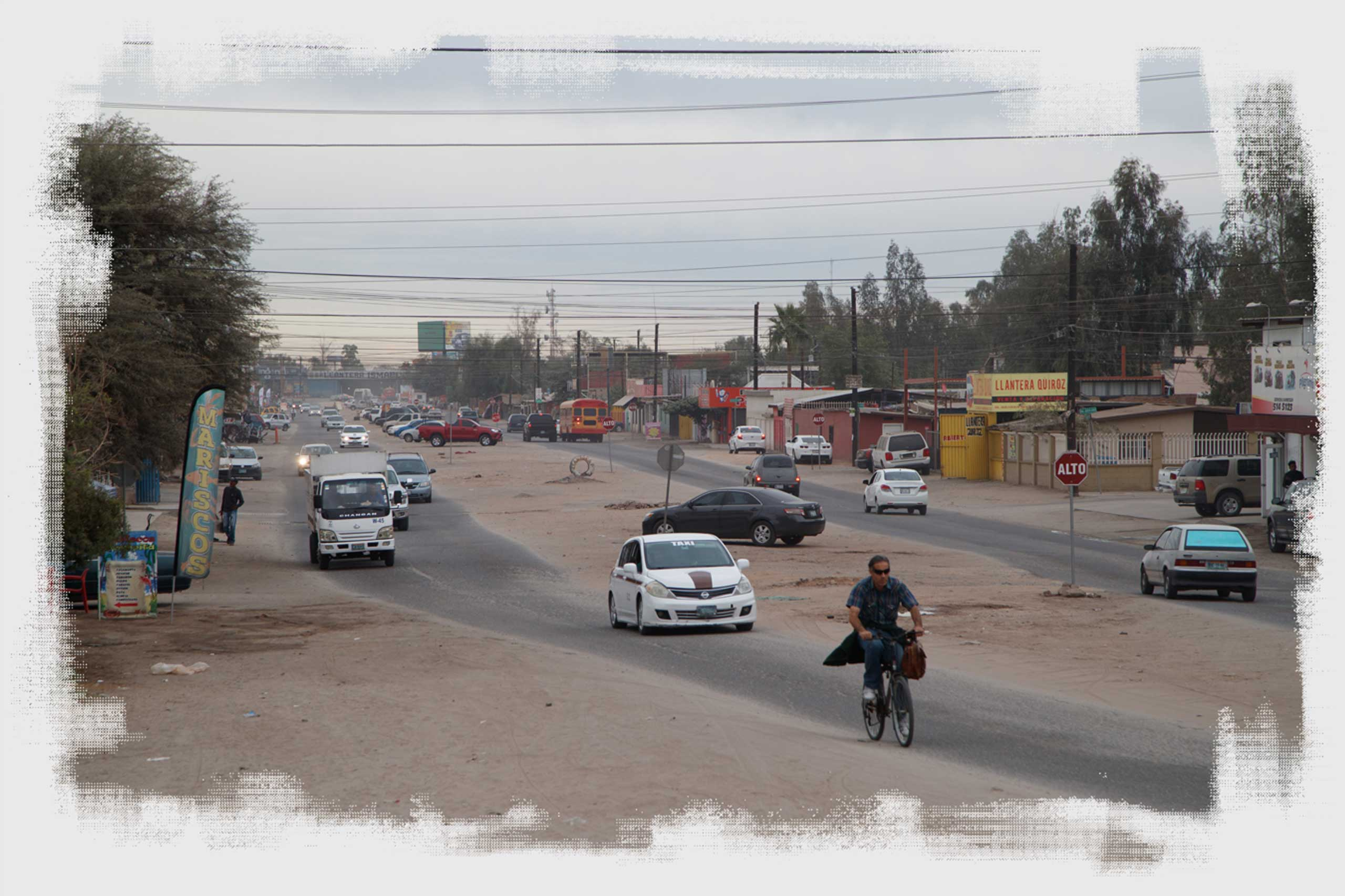 A man rides a bicycle on a busy street in the neighborhood Colonia Vicente Guerrero in Mexicali.