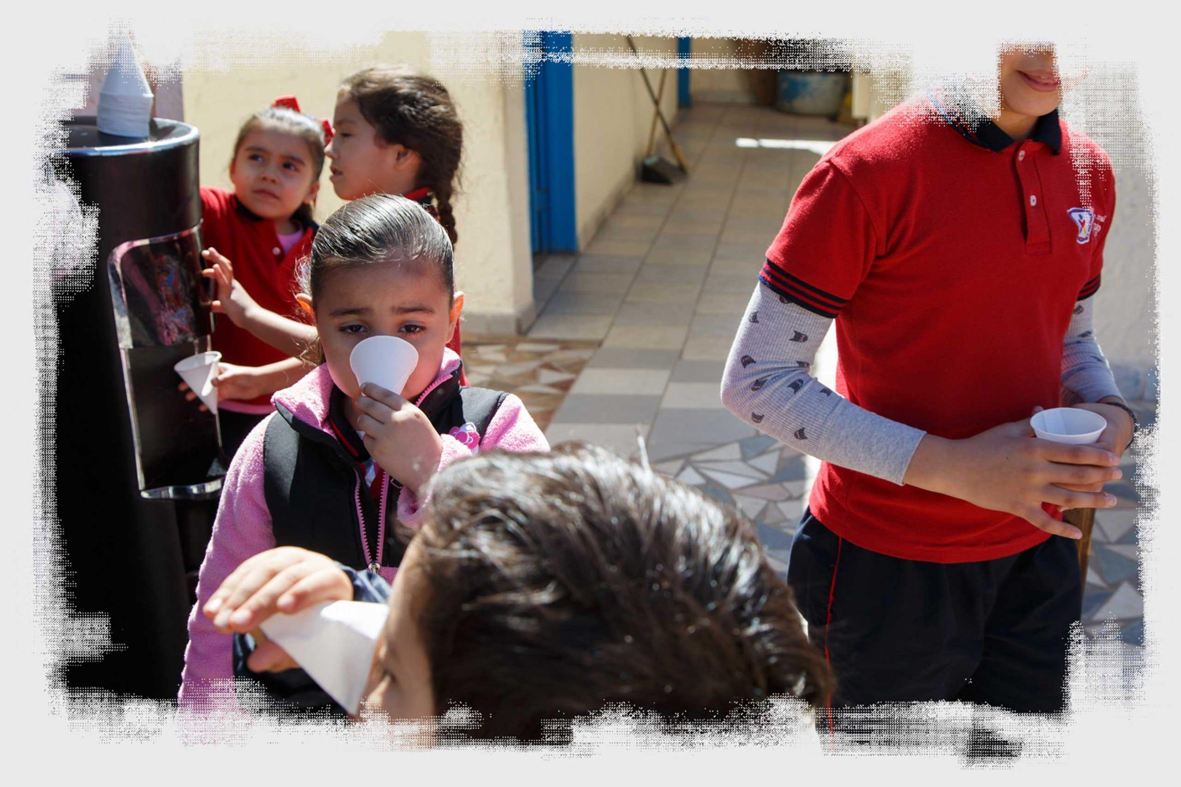 Estudiantes beben agua fría de un dispensario eléctrico en el Colegio Integral Leonardo da Vinci en Mexicali.