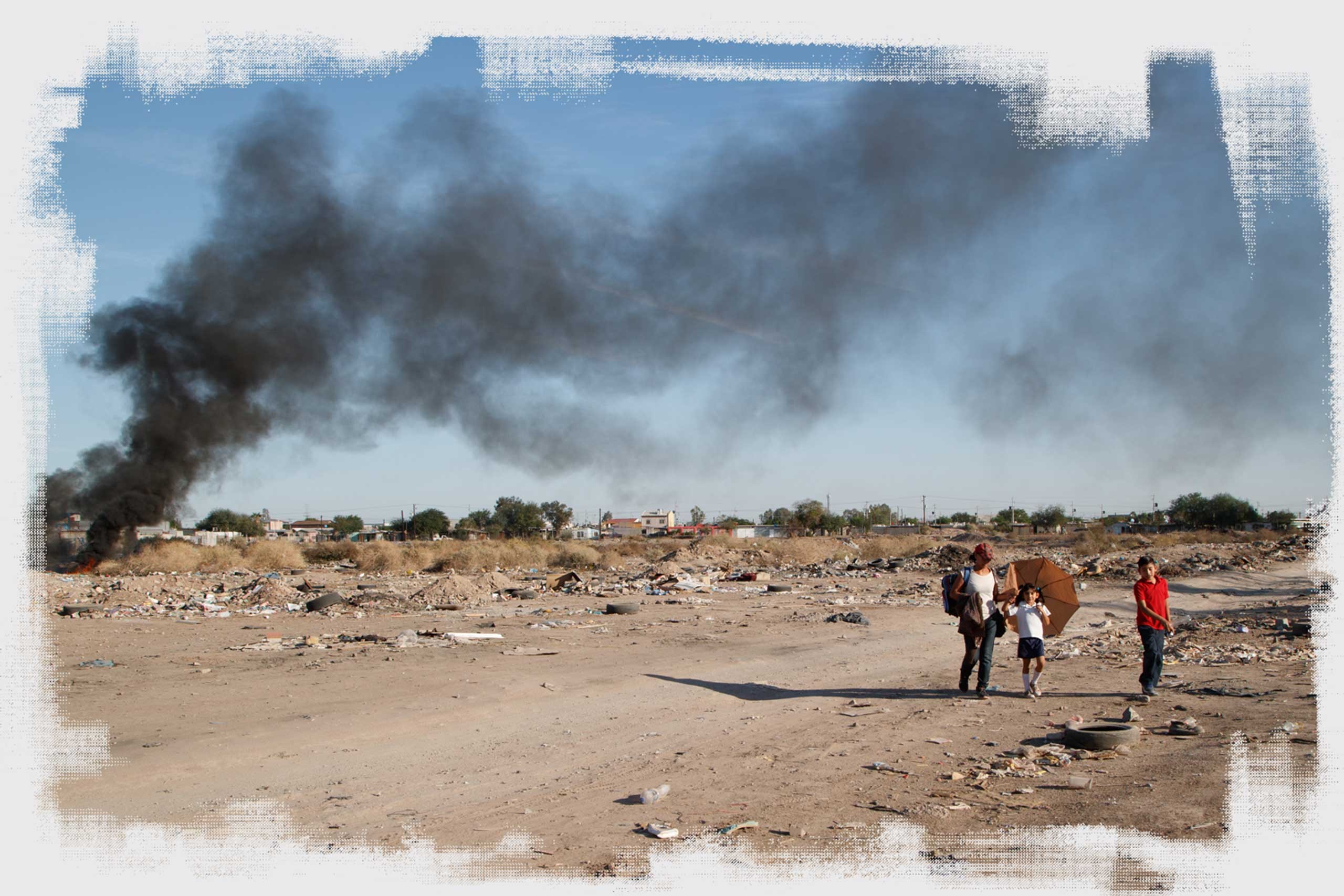 A woman walks two children home from school through a vacant lot in Mexicali, passing a heap of burning tires and trash.